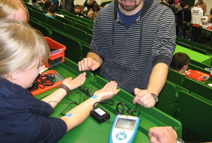 Students in a lecture hall work in small groups with an ECG monitor