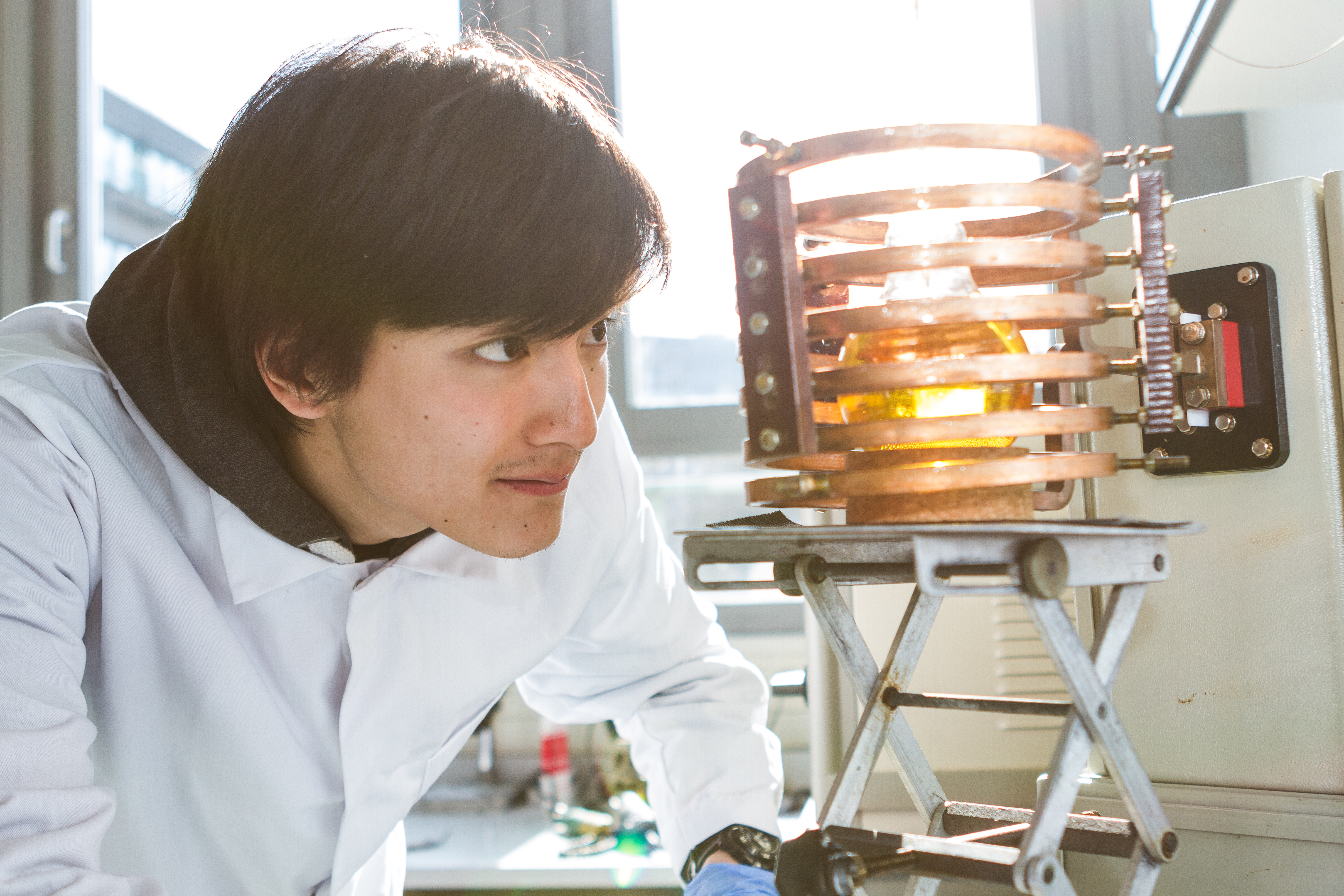 Student looks at a coil filled with magnetic nanoparticles