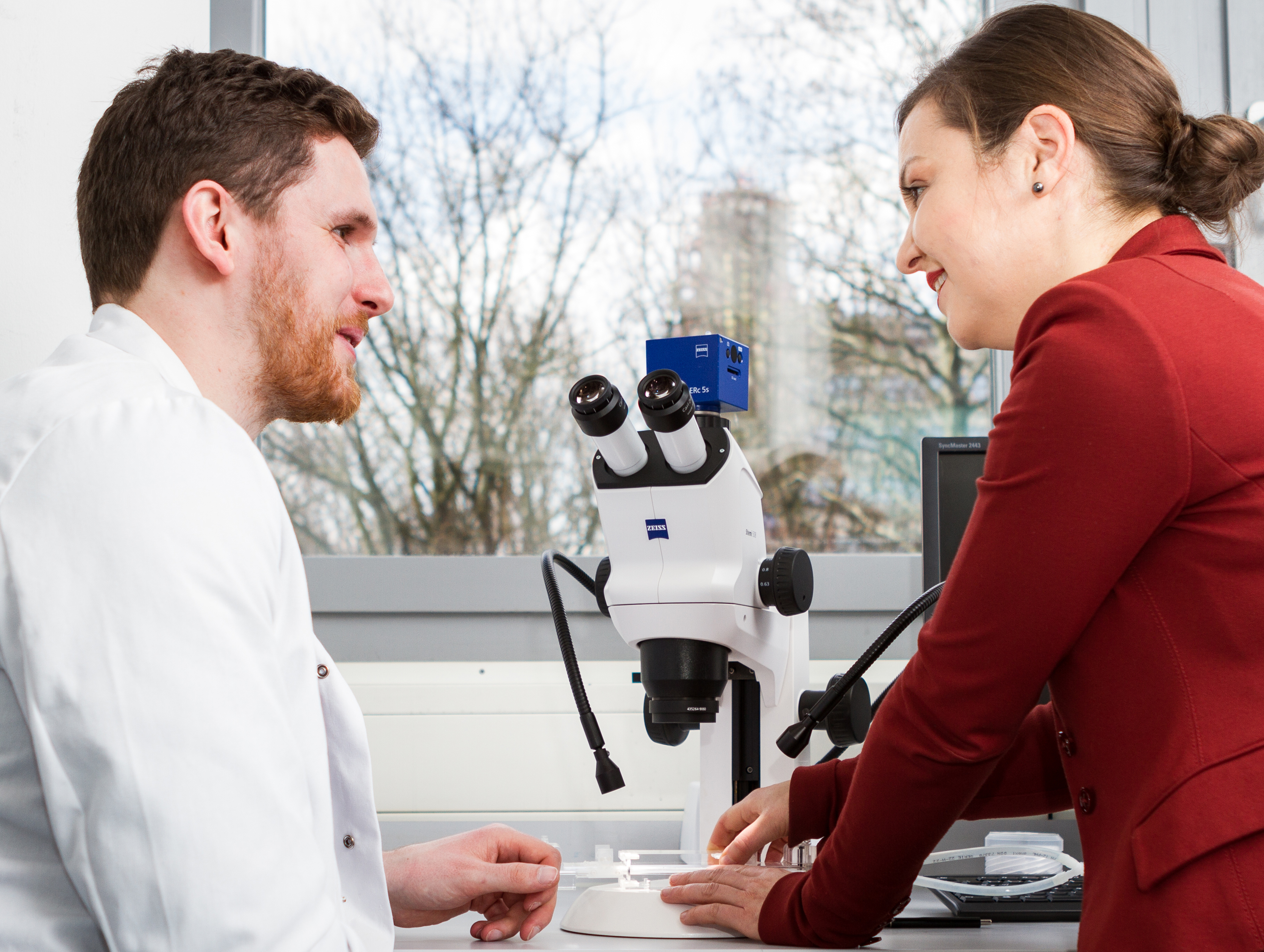 Two scientist at a light microscope